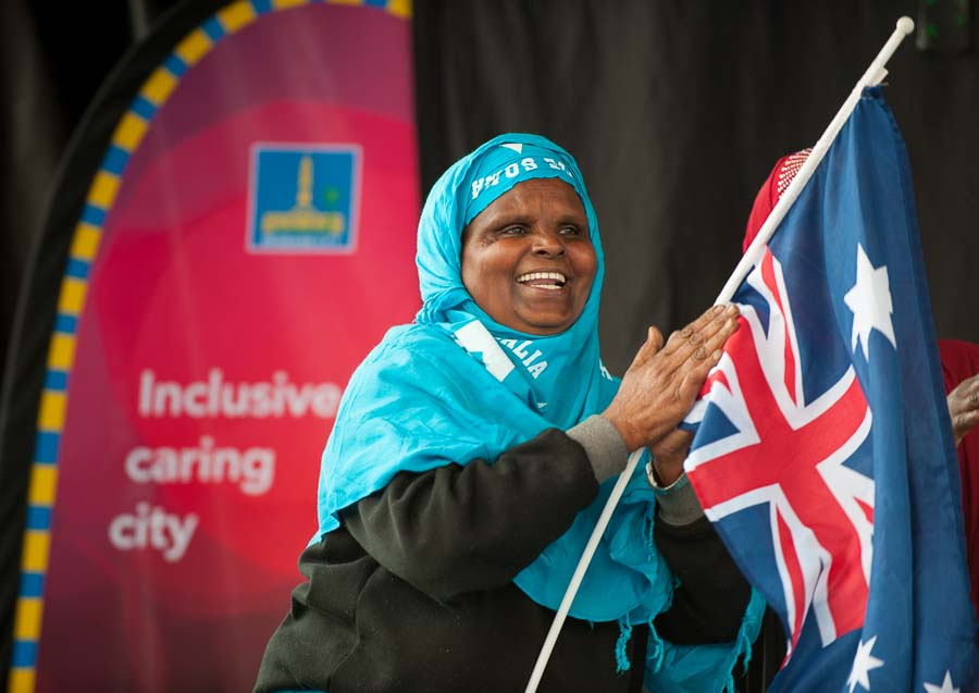 A lady smiles and claps holding an Australian flag in Brisbane