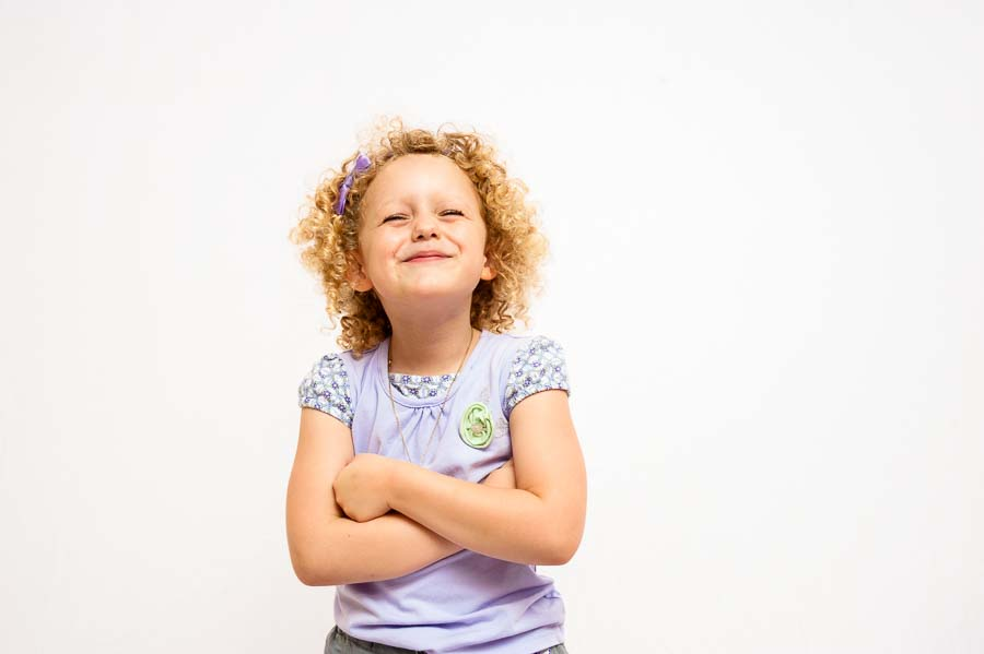 a child stikes a sassy pose with a white background