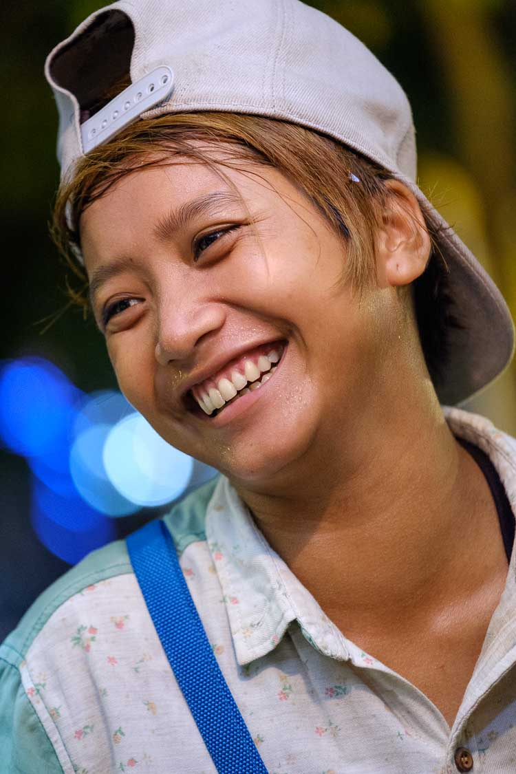 Portrait of a street vendor laughing at night in Cambodia