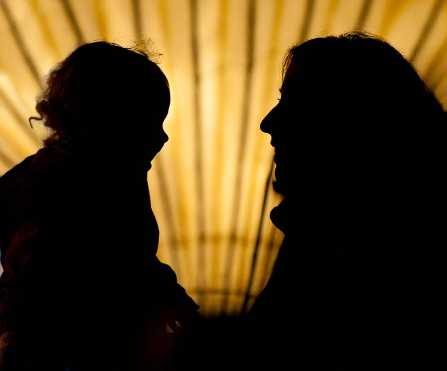 Silhouette of mother and child at a candlelight event