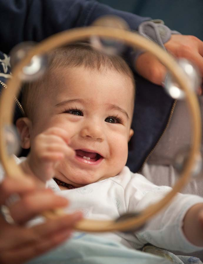 A baby smiles at a toy while playing with a carer
