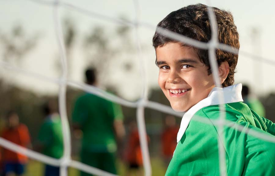A boy playing as soccer goalkeeper smiles from behind the net